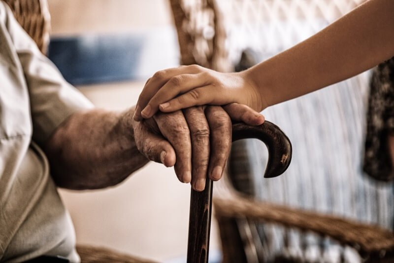 Young african american grand daughter holding her grand parents hand.
