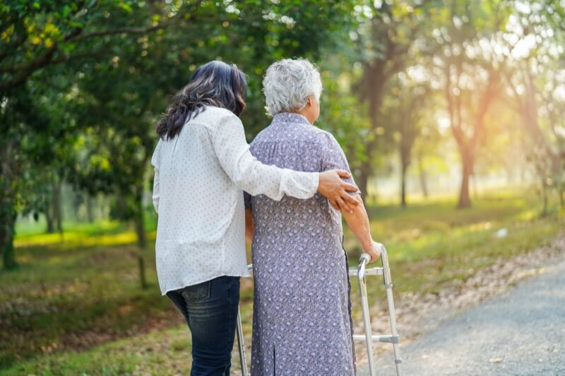 Elderly Asian woman walking with her nurses aide