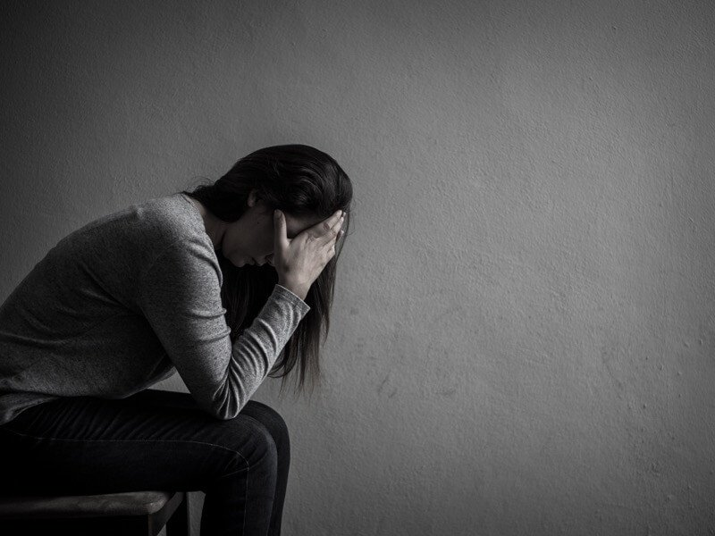 Depressed woman with her face in her hands