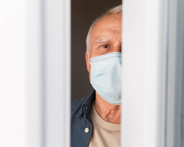 Senior man, wearing a medical mask, looking between the blinds of a window