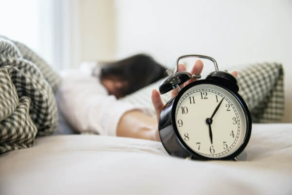 Woman waking up reaching for an an analog alarm clock to shit it off