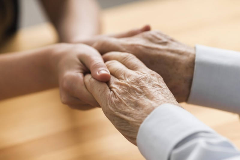Young woman holding the hands of an elderly patient